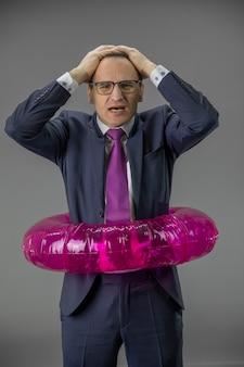 Uomo d'affari depresso in salvagente, le mani sulla testa preoccupate per la caduta degli stock