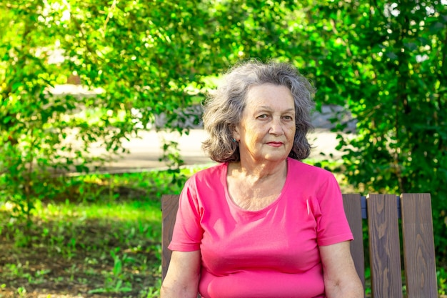 Donna anziana depressa premurosa mentre è seduto su una panchina del parco in una giornata di sole estivo. una donna matura con una maglietta luminosa pensa a cose tristi. psicologia. espressione seria e premurosa