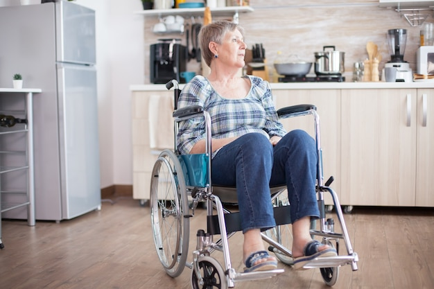 Donna anziana handicappata depressa in sedia a rotelle dall'infortunio alla gamba. pensionato anziano disabile in riabilitazione, paralisi e disabilità per invalido pieno di dolore, preoccupazione e faccia triste. periodo di pensionamento per ol