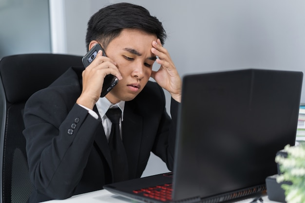 Uomo depresso in completo parlando su smartphone