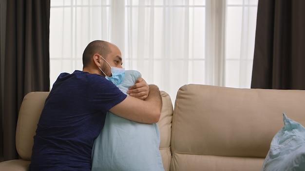 Uomo depresso con maschera di protezione contro il covid-19 che abbraccia un cuscino durante l'autoisolamento