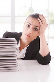 Depresso e oberato di lavoro. giovane donna depressa in tuta che guarda la telecamera e tiene la testa in mano mentre è seduta al tavolo con una pila di documenti appoggiata su di essa