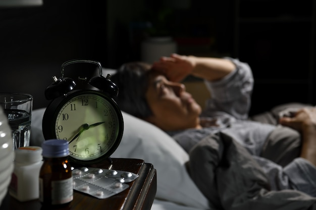La donna senior depressa sdraiata a letto non riesce a dormire dall'insonnia. messa a fuoco selettiva sulla sveglia