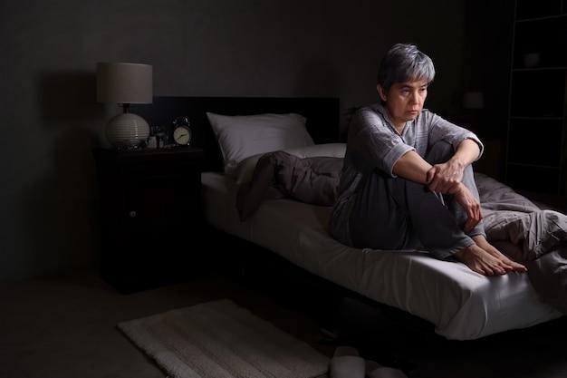 La donna senior depressa che si siede nel letto non può dormire dall'insonnia