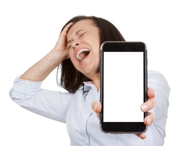 Bella donna depressa, stressata, in preda al panico, scioccata e urlante quando si utilizza il telefono cellulare con schermo vuoto per il tuo design su sfondo bianco
