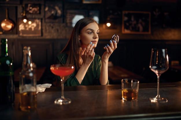 Donna depressa beve alcolici al bancone del bar