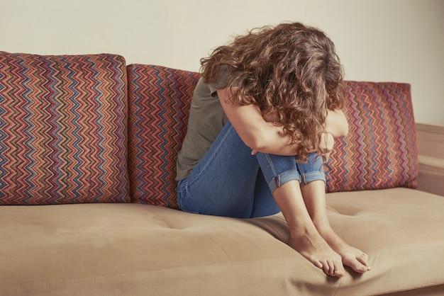 La donna depressa si siede sul divano in salotto. donna triste sola piega in giù la testa. concetto di depressione e stress