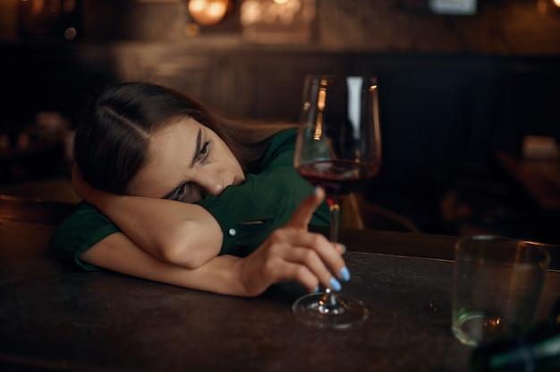 Donna depressa seduta al bancone del bar, posacenere pieno. una donna in un pub, emozioni umane, attività ricreative, depressione