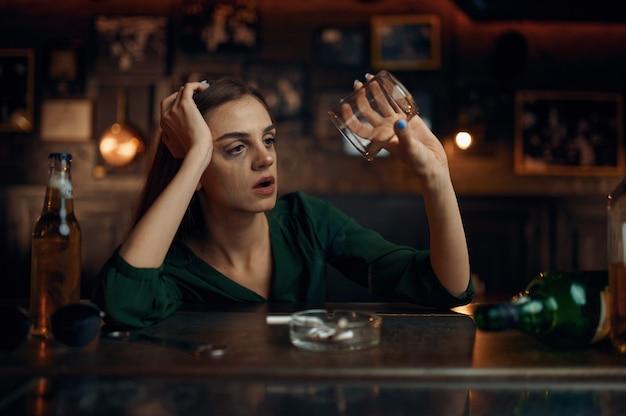 Donna depressa seduta al bancone del bar, posacenere pieno