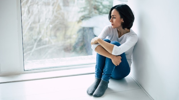 Donna depressa con taglio di capelli corto che piange mentre si tocca il viso. ragazza che urla con gli occhi chiusi a causa della sua malattia mentale.