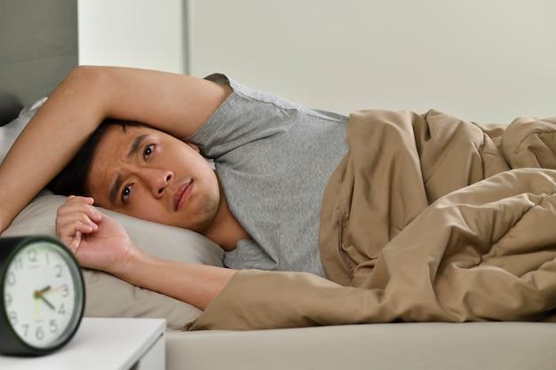 Un giovane asiatico depresso sdraiato a letto non riesce a dormire per l'insonnia