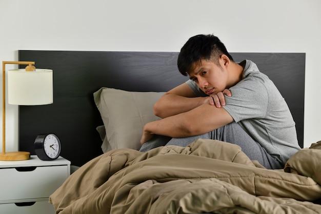 Un giovane asiatico depresso seduto a letto non riesce a dormire per l'insonnia