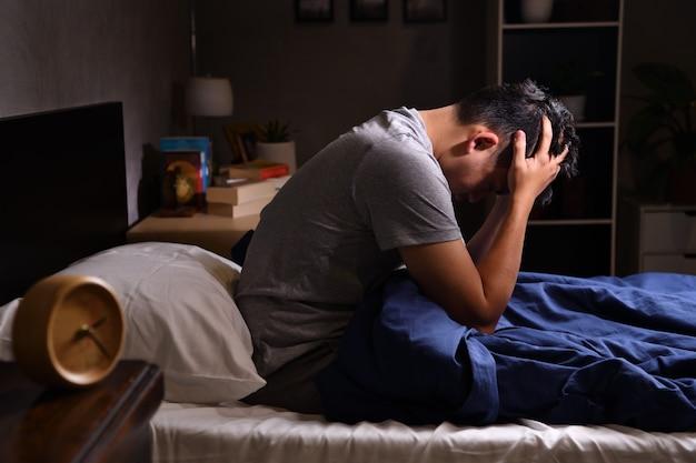 Un giovane depresso che soffre di insonnia seduto a letto
