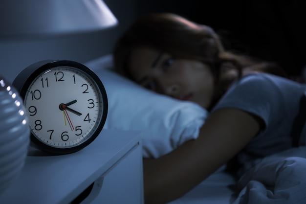 La giovane donna depressa sdraiata a letto non riesce a dormire per l'insonnia. messa a fuoco selettiva sulla sveglia