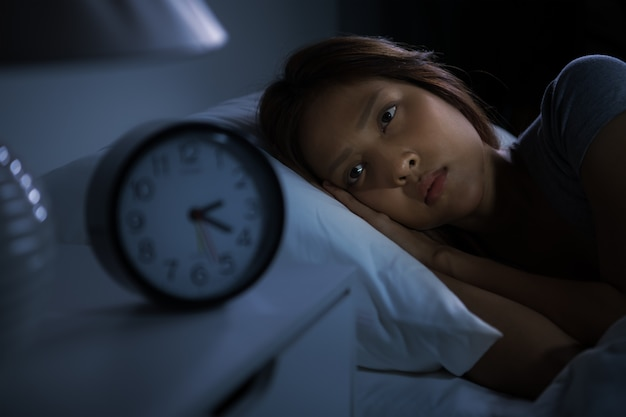 La giovane donna depressa sdraiata a letto non riesce a dormire per l'insonnia