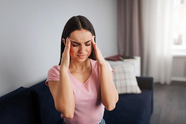 La giovane donna depressa si siede sul sofà. tiene le mani sulla testa. il modello ha mal di testa. lei soffre.