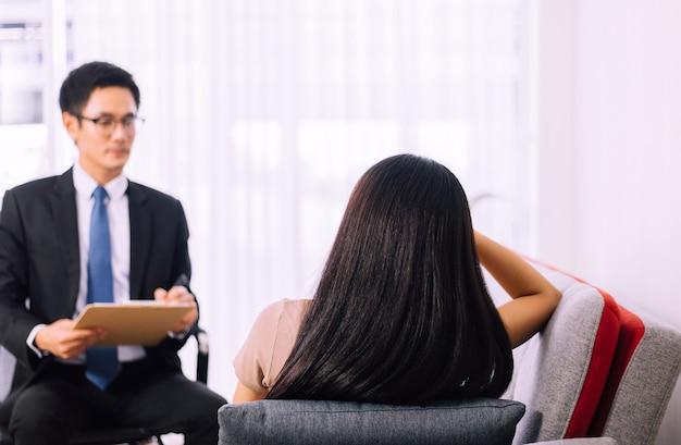 Donna asiatica di depressione che parla con lo psicologo dell'uomogiornata mondiale della salute mentale