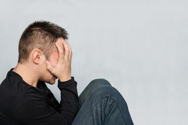 L'uomo della depressione si siede sul pavimento. uomo con mal di testa e stanchezza. un malato nasconde il viso. nascondere le lacrime. stanchezza, spossatezza, spossatezza, spossatezza, sfinimento
