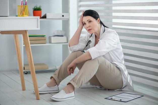 Depressione. sconvolto medico donna in camice bianco e pantaloni seduto sul pavimento con le spalle alla finestra, nel suo ufficio.