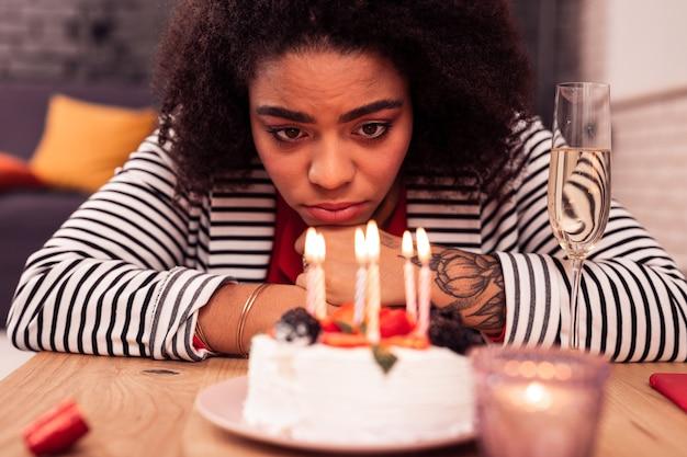 Compleanno depressivo. cupa donna infelice guardando le candele mentre festeggia il suo compleanno da solo