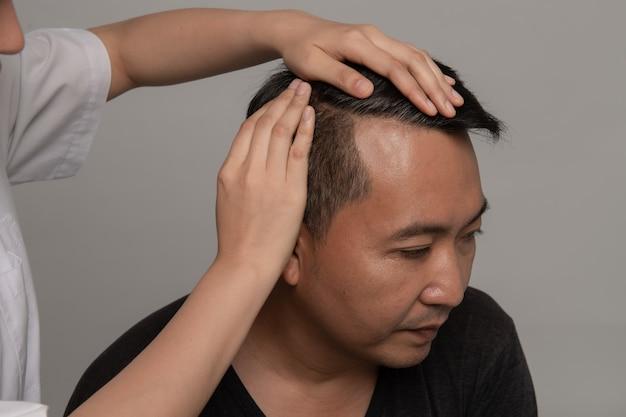 Dermatologo che controlla il problema asiatico di perdita di capelli di preoccupazione dei capelli grigi dell'uomo dei capelli del paziente per il concetto dello sciampo di sanità. Foto Premium