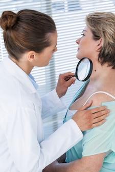 Talpa d'esame del dermatologo con lente d'ingrandimento