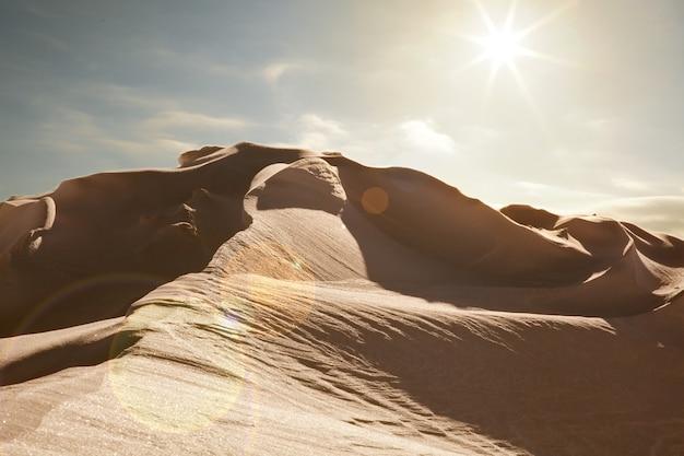Paesaggio desertico con cielo azzurro e sole