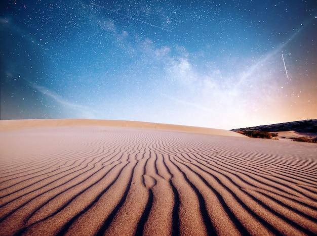 Abbandoni le dune di sabbia nella notte, nelle stelle e nella via lattea, astrophoto profondo del cielo