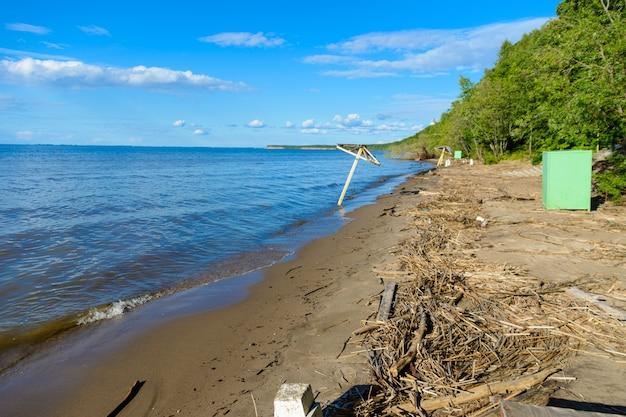 Spiaggia deserta. panchine, ombrelloni, tavoli, spogliatoi abbandonati su una spiaggia sabbiosa dopo le vacanze estive.