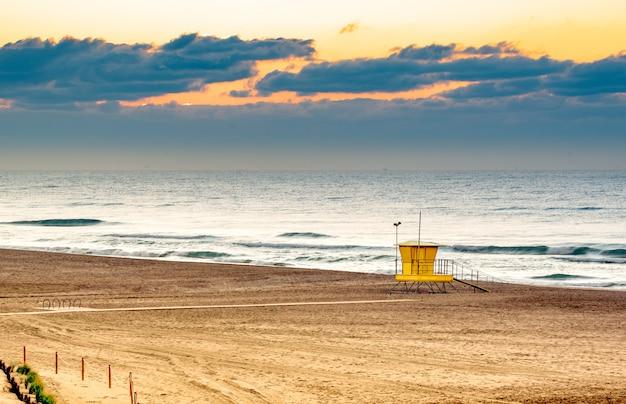 Spiaggia deserta con capanna, tramonto
