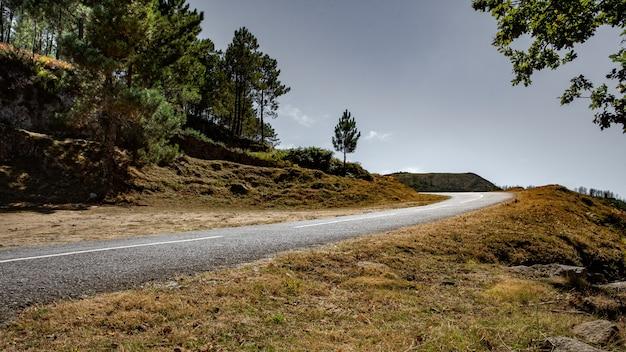Strada di montagna deserta in una giornata grigia e nuvolosa