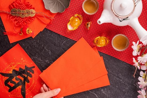 Concetto di design del nuovo anno lunare cinese di gennaio - donna che tiene, dando buste rosse (ang pow, hong bao) per soldi fortunati, vista dall'alto, disteso, sopraelevato. la parola
