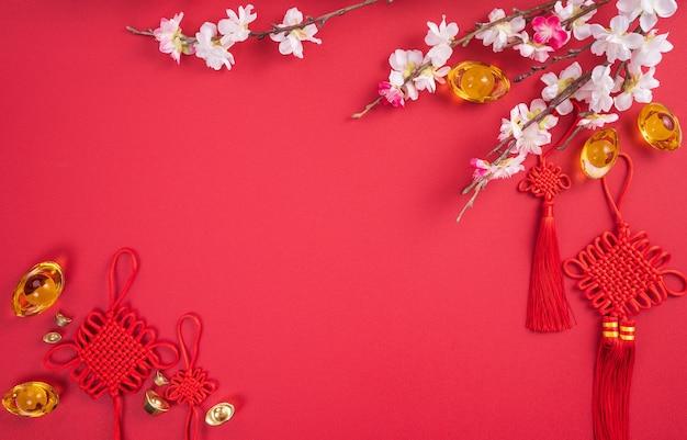 Concetto di design del capodanno lunare cinese - bellissimo nodo cinese con fiori di prugna isolato su sfondo rosso, piatto laico, vista dall'alto, layout overhead.