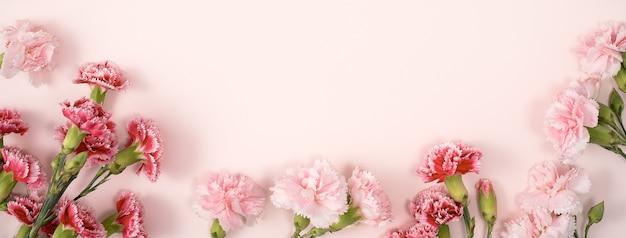Concetto di design del design di saluto di festa della mamma con bouquet di garofani sul fondo della tavola rosa pastello