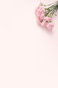 Concetto di design del design di auguri per la festa della mamma con bouquet di garofani su sfondo tavolo rosa pastello