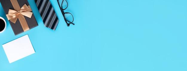 Concetto di design vista dall'alto dell'idea regalo festa del papà con saluto mockup in bianco bianco sul fondo della tavola blu.