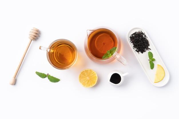 Concetto di design vista dall'alto di miele tè nero con limone giallo e foglia di menta su sfondo bianco da tavola.