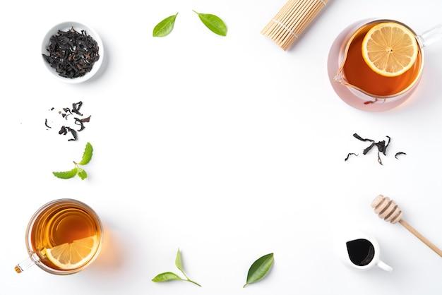 Concetto di design vista dall'alto di tè nero al miele con foglia di menta e limone giallo su sfondo bianco da tavola.