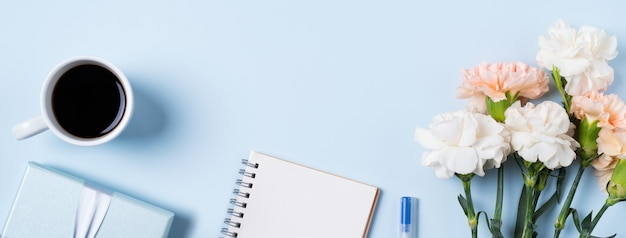 Design concpet del saluto della festa della mamma con fiore di garofano, idea regalo per le vacanze e diario del taccuino sullo sfondo della scrivania della madre.