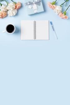 Design concpet del saluto della festa della mamma con fiore di garofano, idea regalo per le vacanze e diario del taccuino sullo sfondo della scrivania delle madri.