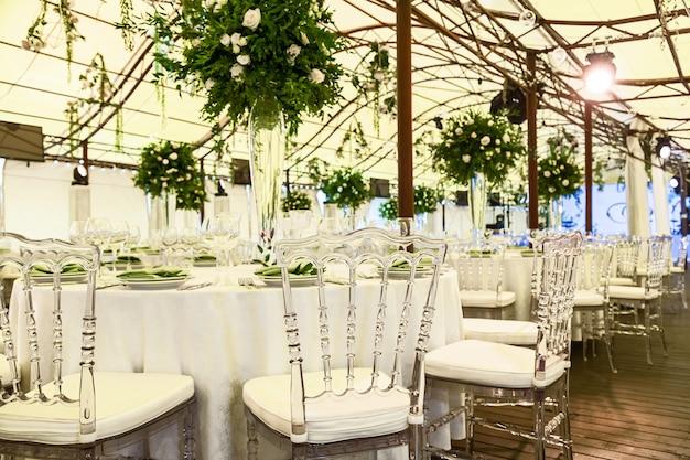 Design e decorazione della celebrazione del matrimonio con rose bianche, foglie verdi, candele e mazzi di fiori