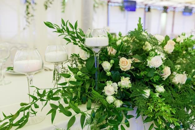 Design e decorazione della celebrazione del matrimonio con rose bianche foglie verdi candele a