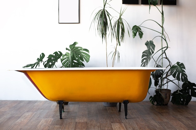 Progettazione del loft interno del bagno o della camera. pareti bianche con copyspace libero. trend verde - foglie di palma sullo sfondo. bagno giallo dal design moderno.
