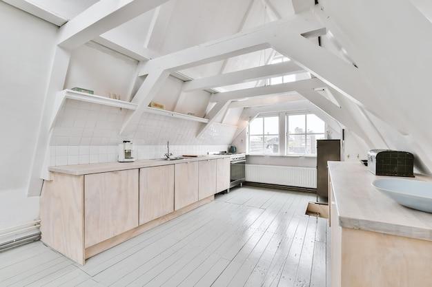 Design della cucina mansardata con armadi in legno e interni minimalisti sotto le travi del tetto