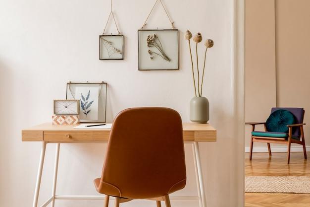 Progetta interni scandinavi di uno spazio per l'home office con finte cornici per foto, scrivania in legno, sedia marrone, forniture per ufficio e accessori personali. home staging neutro ed elegante. modello.