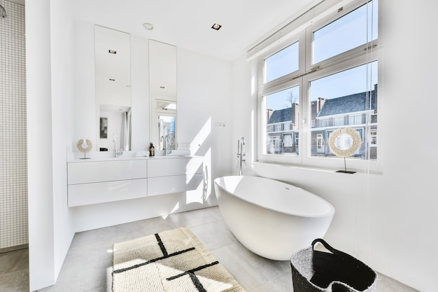 Progettazione di un bagno spazioso illuminato dal sole con doppio lavabo e specchio e grande vasca da bagno bianca vicino alle finestre