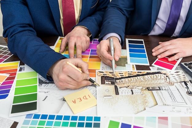 Gruppo di progettazione che lavora all'ufficio nell'ambito del progetto della casa. appartamento scetch con tavolozza dei colori. dolce casa moderna. Foto Premium