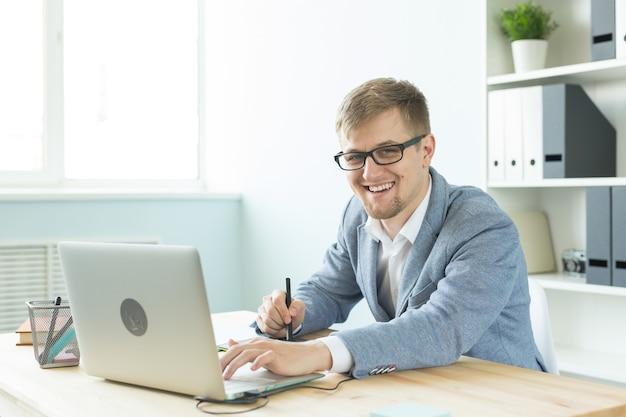 Progettista, artista e concetto di web design - ritratto di giovane uomo utilizzando tablet con penna digitale e laptop in ufficio.