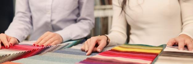 Designer e cliente che scelgono il tessuto nel concetto di interior design del primo piano del catalogo
