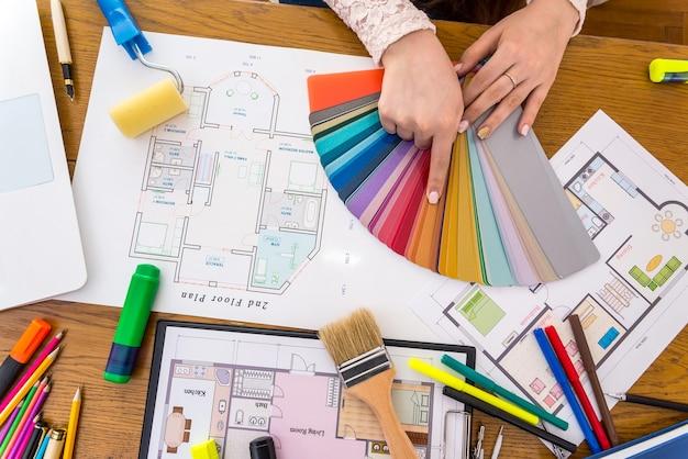 Mani del progettista che scelgono il colore sul campione, primi piani